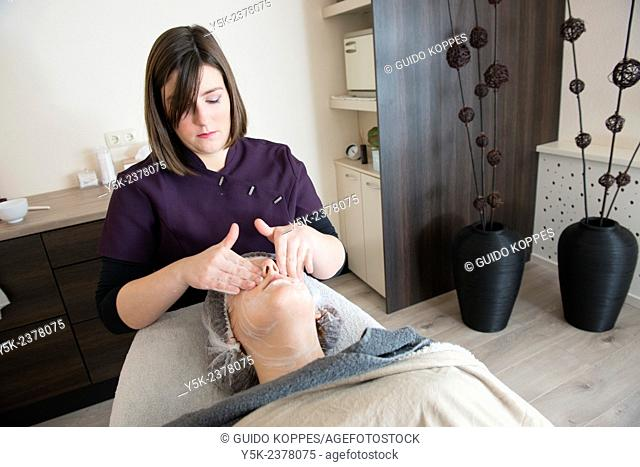 Tilburg, Netherlands. Young beautician applying a massage to the facial skin of her customer