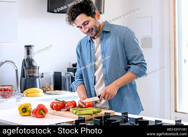 Smiling mid adult man cutting tomatoes in kitchen at home