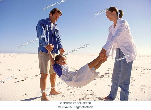 beach-scene, full-figure, father and mother are holding their daughter at hands and feet swinging her up and down  - GERMANY, 11/09/2004