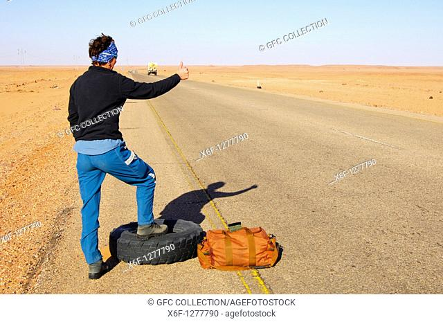 Woman standing with a travelling bag next to a flat tyre at the edge of a lonly country road trying to stop a car for help, Al Awaynat Libya
