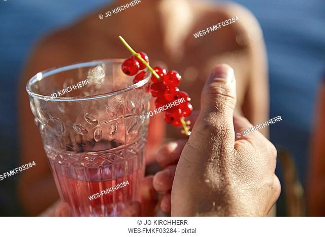 Hand holding a drink with red currants