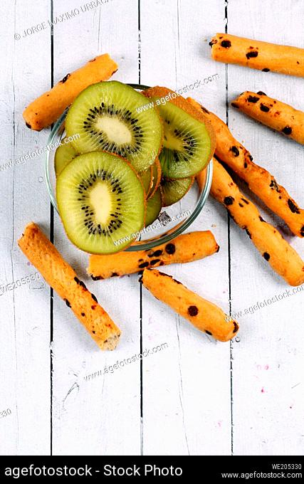 Chocolate sticks with kiwi slices on a white wooden board