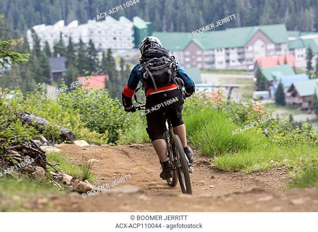 A mountain biker negotiates the Green Mile bike trail at Mt. Washington, The Comox Valley, Vancouver Island, British Columbia, Canada