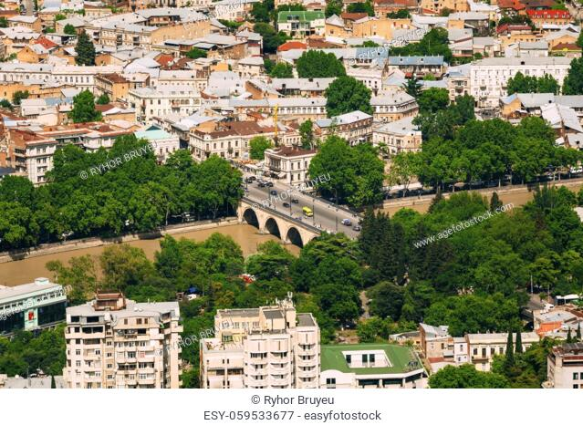 Tbilisi, Georgia. Aerial View Of Arch Bridge Over Kura Mtkvari River, Surrounded By Residential Area In Sunny Summer Day