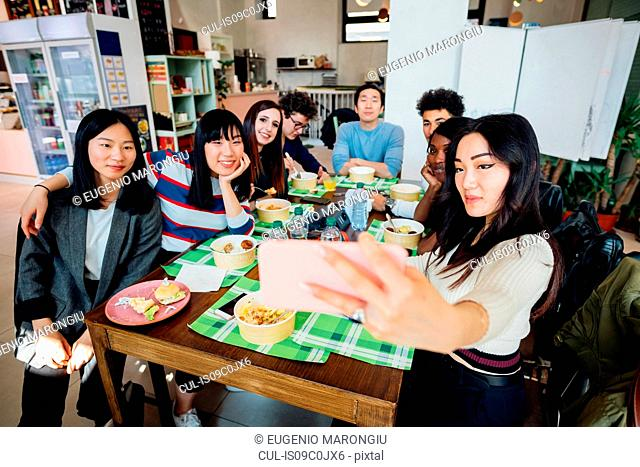Young male and female business team having working lunch at cafe table, taking smartphone selfie