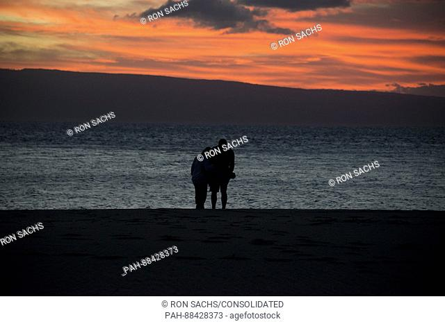 Two unidentified people on the beach at sunset looking towards the Hawaiian island of Lanai from Kaanapali Beach, Maui, Hawaii on Thursday, February 23, 2017