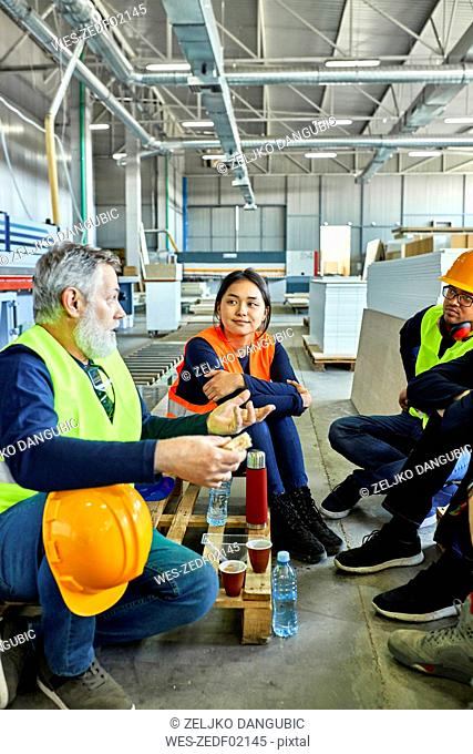 Workers in factory having lunch break together