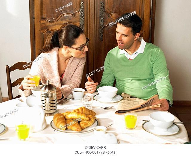 Couple sitting at breakfast table, talking