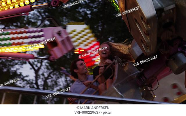 Tracking shot, medium shot of young couple on amusement park ride / American Fork, Utah, United States