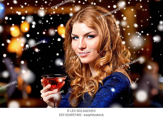 new year party, christmas, winter holidays and people concept - glamorous woman with cocktail at night club or bar over snow