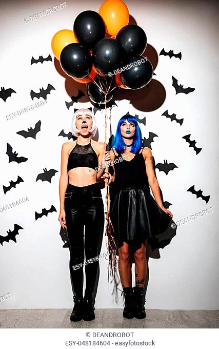 Image of two emotional young women in halloween costumes on party over white background with balloons. Looking aside