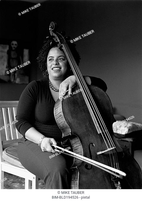 Mixed race woman playing cello
