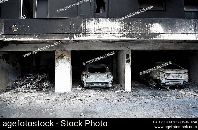 13 July 2020, Berlin: Burnt-out vehicles are parked in a garage in the Neukölln district. Six cars had burned down during the night