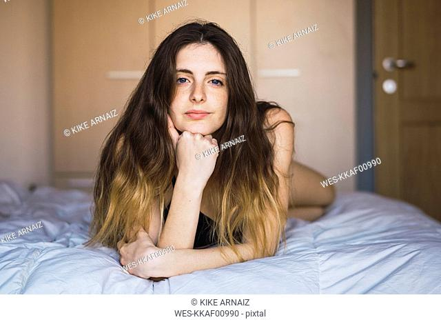 Portrait of young woman hair lying on bed