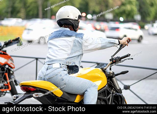 Rear right shot of a young woman riding a yellow motorcycle