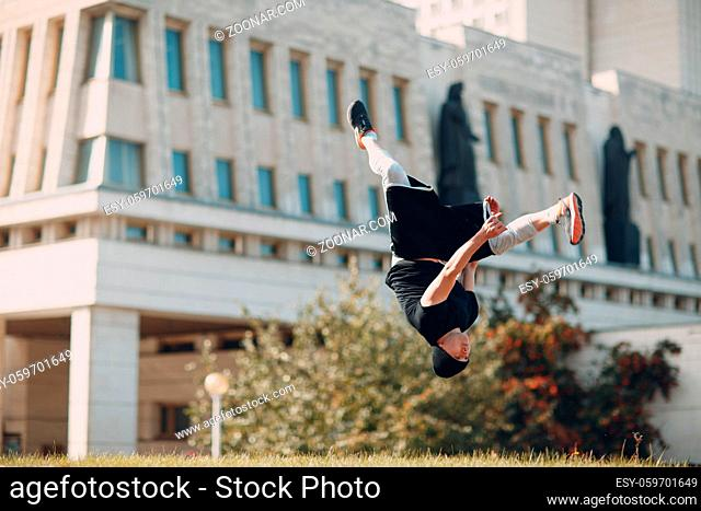 Young sporty guy doing parkour at the city street