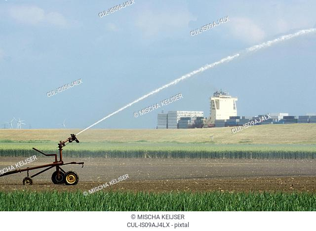 Plant crop irrigation due to prolonged drought. A container ship leaving Antwerp harbour in the background, Rilland, Zeeland, Netherlands