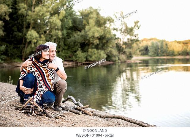 Senior couple at campfire at a lake