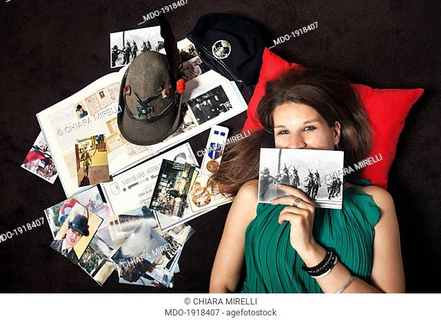 Girl lying near some memorabilia and Alpine hat and showing a photo placed on the face. Dolo (Italy), April 2014