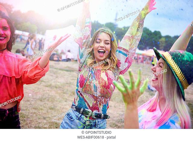 Friends dancing during music festival, colour powder