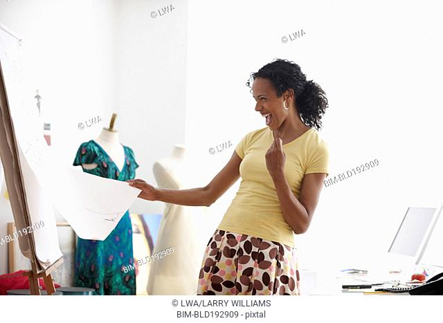 African woman laughing at sketch in design studio