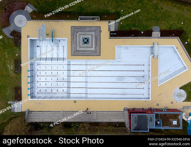 PRODUCTION - 19 April 2021, Hessen, Bad Soden am Taunus: A pool employee walks through the empty pool of the outdoor pool in Bad Soden (aerial view with a...