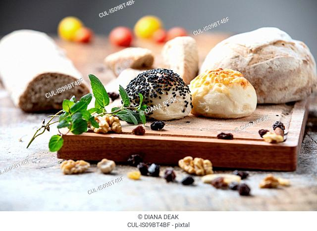 Seeded bread rolls and rustic loaves on chopping board, still life