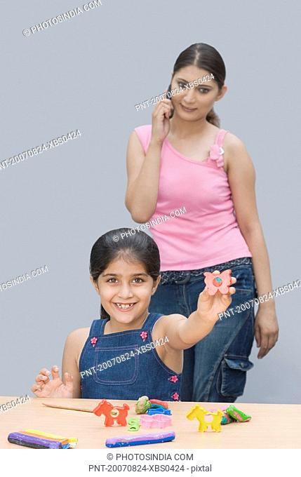 Portrait of a girl smiling and her mother talking on a mobile phone behind her