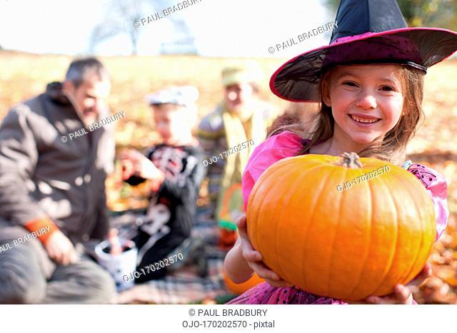 Girl in Halloween costumes holding pumpkin