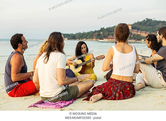 Thailand, Koh Phangan, group of people sitting on a beach with guitar