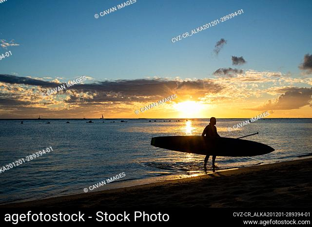 Stand up Paddler walks out of hawaii ocean at sunset