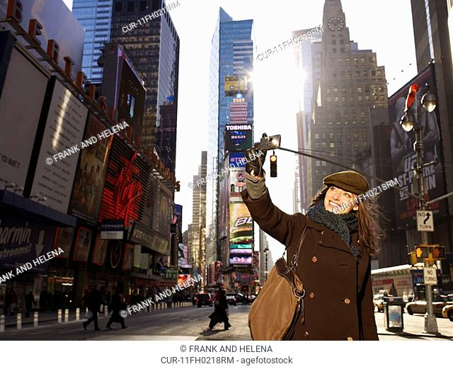 Woman standing in Times Square, New York. She is smiling and taking a picture