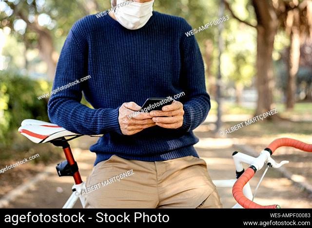 Man with protective face mask leaning on bicycle while using mobile phone on road