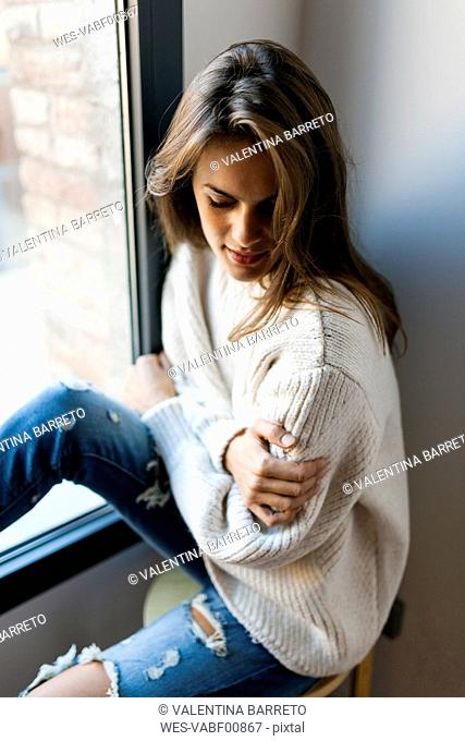 Young woman sitting at a window