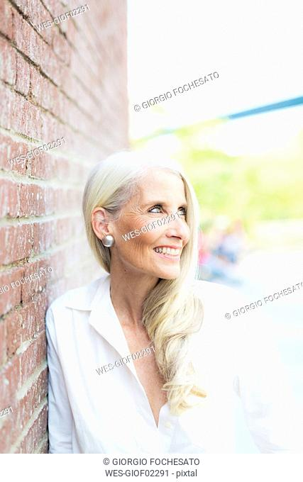Portrait of smiling mature woman wearing white shirt blouse leaning against brick wall