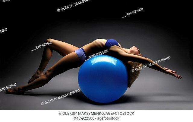 Artistic photo of a woman balancing on exercise ball