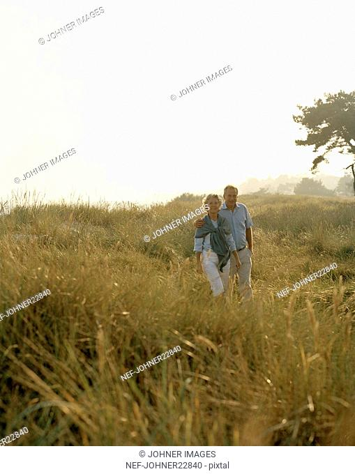 Couple walking together through meadow