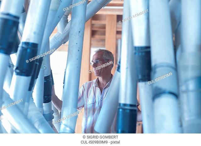 Male miller monitoring milling machine pipes at wheat mill