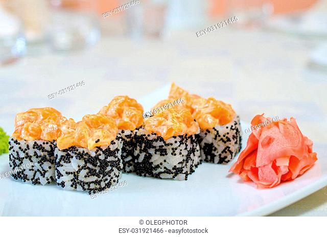 Rolls, sushi and ginger on a white plate and a light background