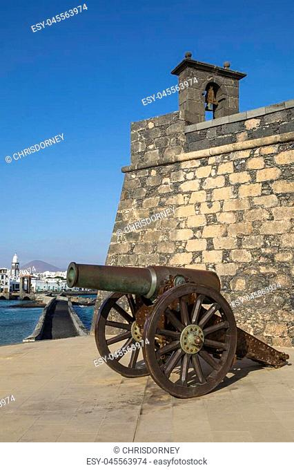 A view of the historic Castillo de San Gabriel in Arrecife, on the volcanic island of Lanzarote, Spain. The tower of the church of San Gines is in the...