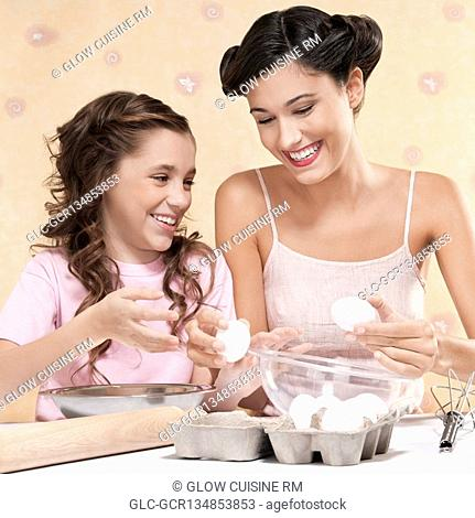 Girl helping her mother in cooking
