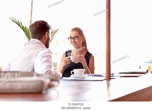 Mature man and woman, sitting outside cafe, drinking coffee, face to face, smiling