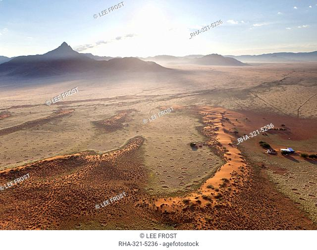 Aerial view from hot air balloon at dawn over magnificent desert landscape of sand dunes, mountains and Fairy Circles, Namib Rand game reserve Namib Naukluft...