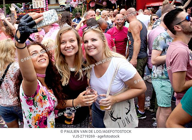 Tilburg, Netherlands, Three girls taking a selfie with a mobile phone during a fair