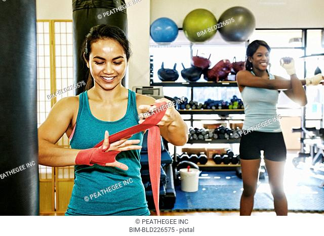 Woman wrapping hand in gymnasium