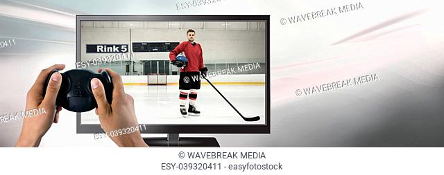 Hands holding gaming controller with hockey player on television