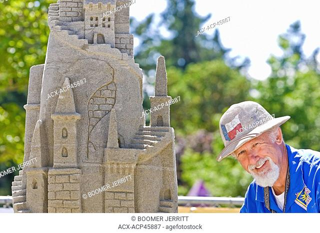 A sand castle competitor with sand sculpture at the annual 'Parksville Beachfest' Canadian open sand castle competition, Parksville, Central Vancouver Island