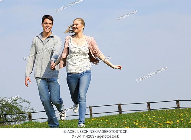 Couple walking on meadow