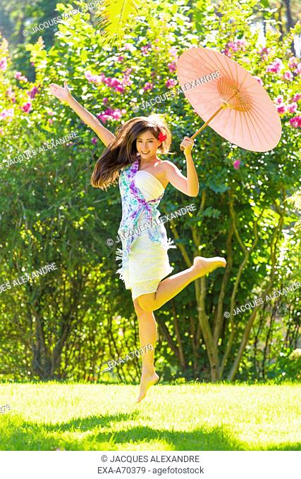 woman dancing in park with umbrella