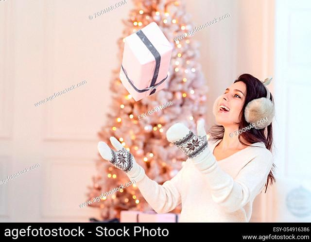 Beautiful young girl in white dress posing on camera. Christmas concept